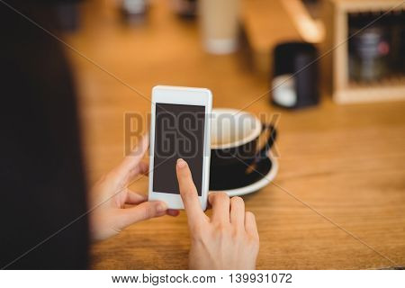 Woman using mobile phone at office cafeteria