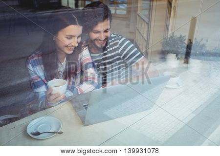 Happy young couple using laptop while having coffee at cafe