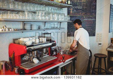 Young male barista working at cafe