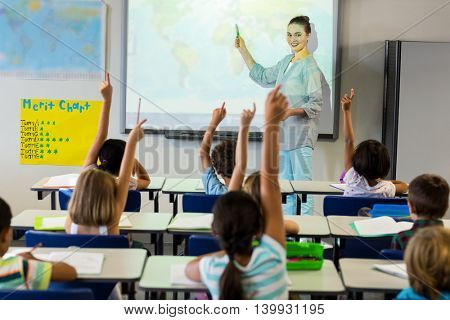 Smiling female teacher teaching schoolchildren using projector screen in classroom