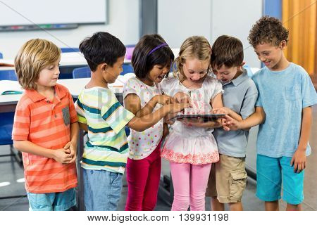 Happy schoolchildren using digital tablet in classroom