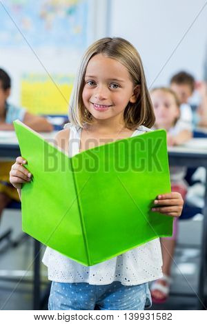 Portrait of happy girl reading book in classroom
