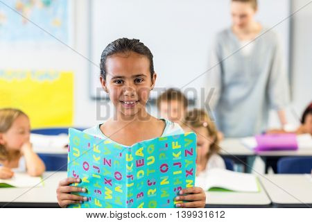Portrait of smiling girl reading book in classroom