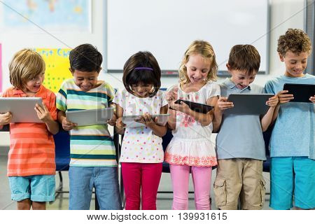 Smiling schoolchildren using digital tablets in classroom
