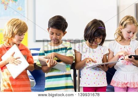 School kids using digital tablets in classroom