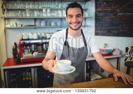 Portrait of confident young male barista serving coffee at cafe