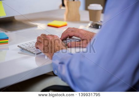 Cropped image of businessman typing on keyboard in office