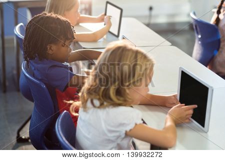 High angle view of schoolchildren using digital tablets in classroom