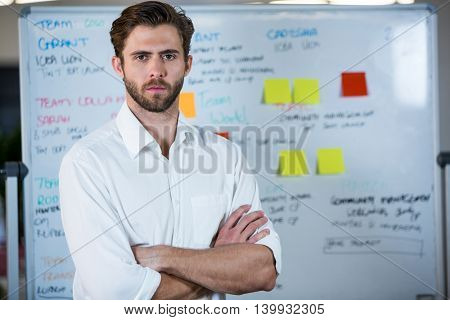 Portrait of confident businessman standing against whiteboard in office
