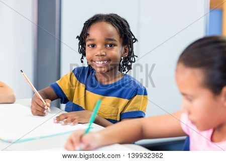 Portrait of smiling schoolboy with classmate writing on book in classroom