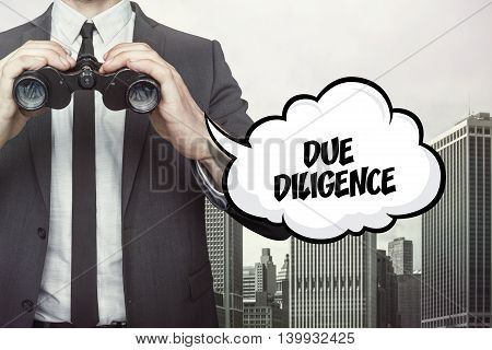 Due diligence text on speech bubble with businessman holding binoculars on city background