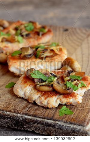Slices of roasted turkey meat. Fried turkey steaks with cheese and mushrooms on a chopping board and an old wooden table. Delicious and easy meat recipe. Closeup