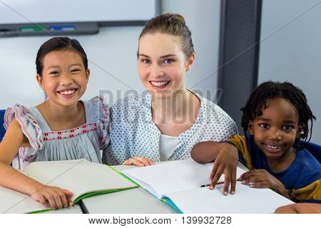 Portrait of happy teacher with schoolchildren in classroom