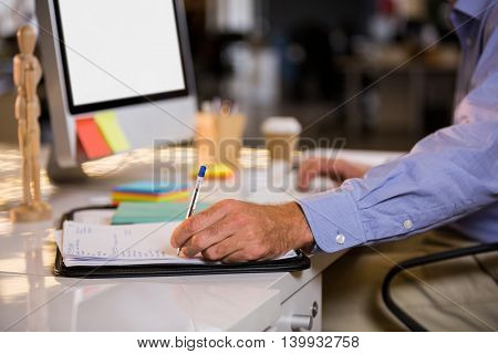 Midsection of businessman writing on paper while sitting at computer desk in office
