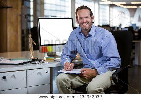 Portrait of happy businessman writing on clipboard by desk in office