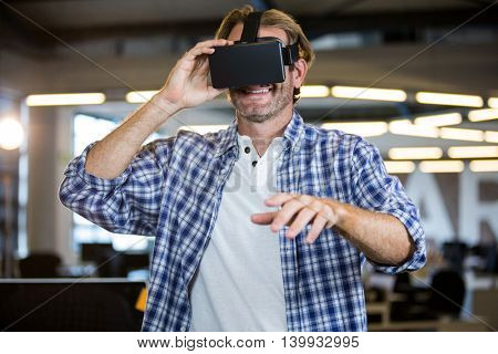 Smiling creative businessman using virtual reality simulator in office