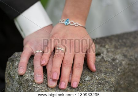 young wedding couple lays hands on each other at old stone fountain