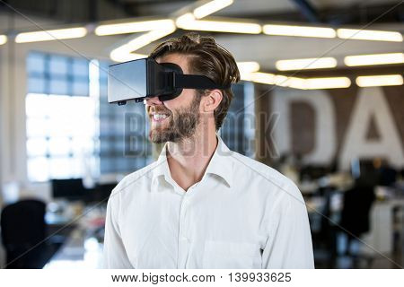 Smilling businessman using virtual reality simulator in office