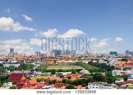 BANGKOK THAILAND - 11 JUNE 2016 - Wat Phra Kaew and Sanam Luang and other traditional Thai architecture buildings against surrounding modern high-rise buildings in Bangkok Thailand.