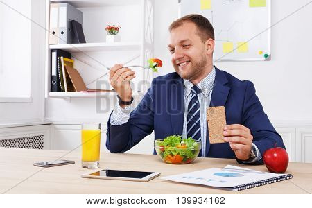 Man has healthy business lunch in modern office interior. Young handsome businessman at working place, looking at fork with vegetable salad in bowl, diet and eating right concept.