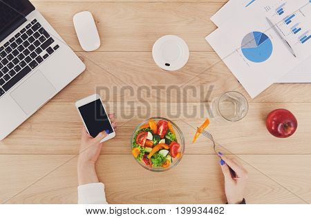 Woman eat business lunch at working place. Businesswoman's hands with fork and mobile on wooden desk in office. Healthy diet food, vegetable salad with apple near laptop and papers. Top view, flat lay
