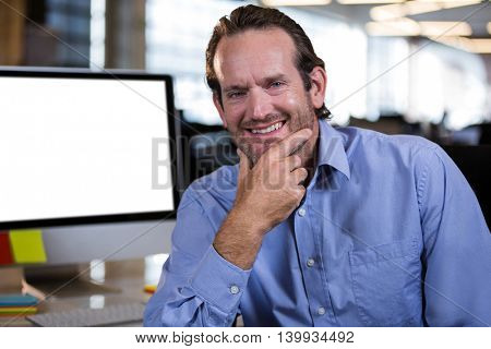 Portrait of confident businessman with hand on chin at computer desk in creative office