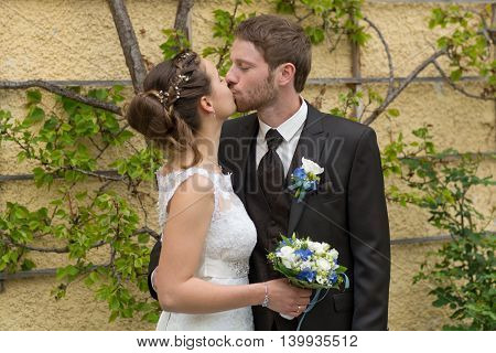 young kissing newlyweds in front of a row of fruit trees