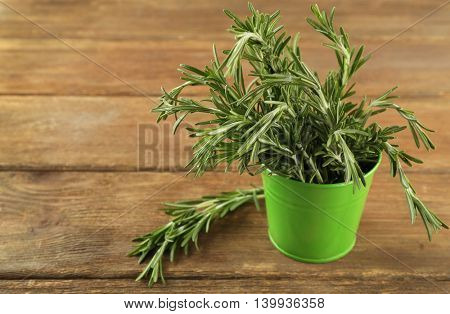 Fresh rosemary in bucket on wooden table
