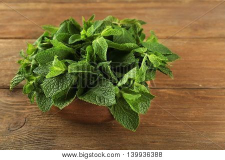 Fresh bunch of mint on wooden table