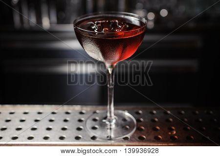 dark cocktail on a dark bar setting. no people
