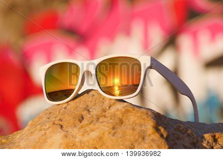 sunglasses with reflected sea sunset lying on rock on background of graffiti
