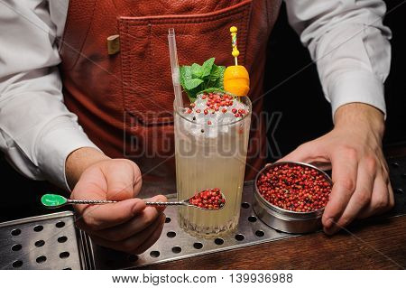 Barman is decorating cocktail with pink pepper no face