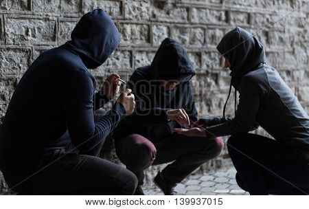 substance abuse, addiction and bad habits concept - close up of young people smoking cigarettes and using drugs outdoors