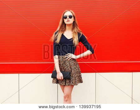 Fashion Beautiful Woman In Leopard Skirt Sunglasses Handbag Clutch Posing Over Red Colorful Backgrou