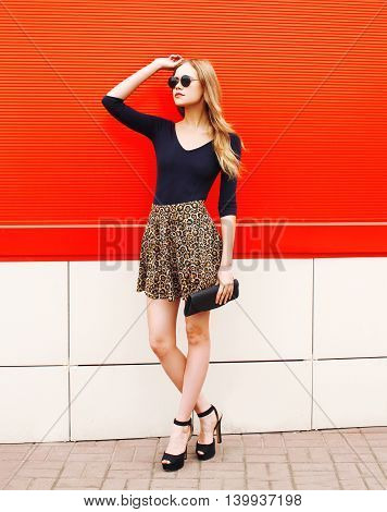 Fashion Beautiful Woman In Leopard Skirt Sunglasses With Handbag Clutch Over Red Background