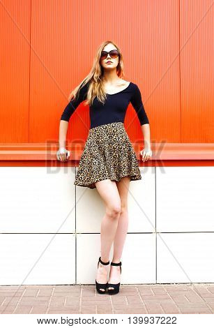 Fashion Beautiful Young Woman In Leopard Skirt And Sunglasses Over Red Background