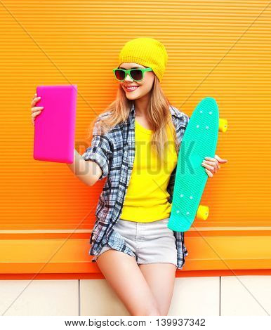 Fashion Pretty Cool Girl Makes Self Portrait On Tablet Pc Over Colorful Orange Background