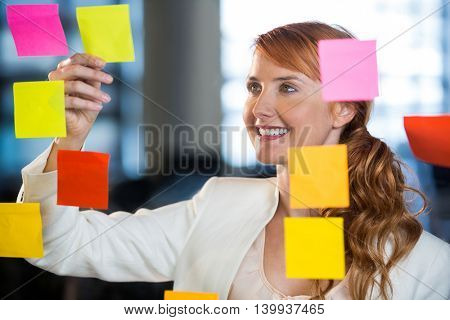 Smiling businesswoman seen through glass with colorful adhesive notes in office