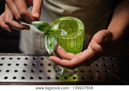 Barman is decorating cocktail with basil no face