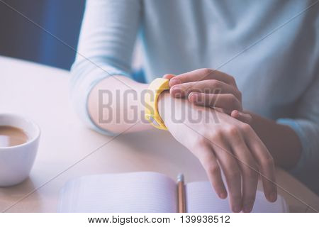What about time. Close up of hands of young woman with tracker coffee and copybook on table