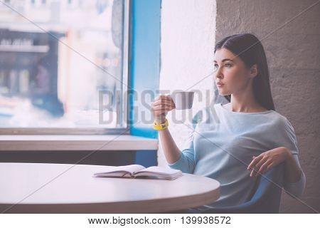 Thoughtful one. Serious and content young woman drinking coffee and planning her future while being in a cafe