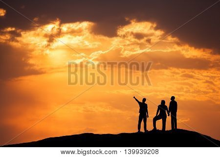 Landscape with silhouette of a standing man pointing finger in colorful sky and his friends on the high mountain peak against the beautiful sunset. High rocks. Travel Climbing Trekking.