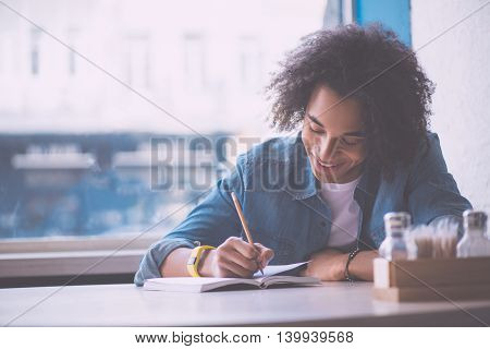 Not to forget. Delighted and positive young man making some notes while sitting in a cafe