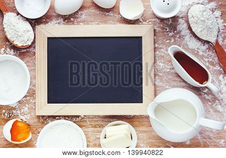 Baking ingredients and pancakes - flour egg butter sugar on wooden table empty space for text on chalkboard toning top view