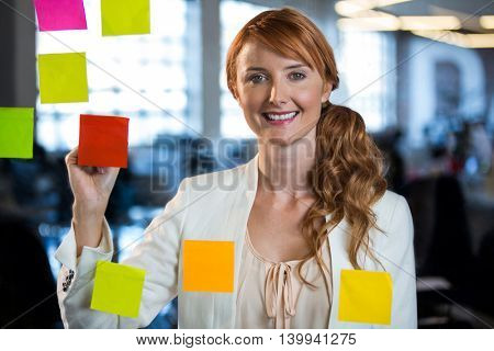 Portrait of businesswoman writing on adhesive notes stuck to glass in creative office