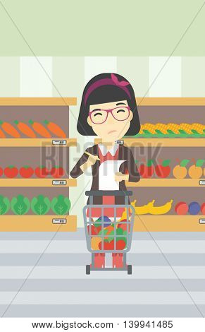 An asian thoughtful woman standing at the supermarket with supermarket trolley full with products and holding a shopping list in hands. Vector flat design illustration. Vertical layout.