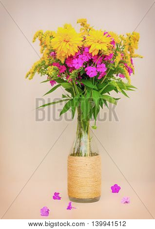 a bouquet of flowers of goldenrod phlox and lilies in a glass bottle on a pink background. toned photo