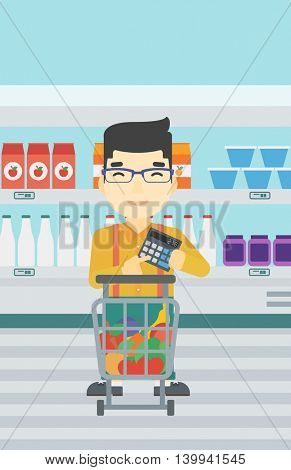An asian young man at the supermarket with calculator and supermarket trolley full with products. Man checking prices with calculator. Vector flat design illustration. Vertical layout.