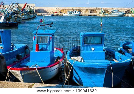 fishing boats anchored in the harbor. Carefully positioned nets and other fishing gear at sea