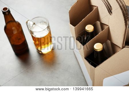 Paper beer package with mug on grey background